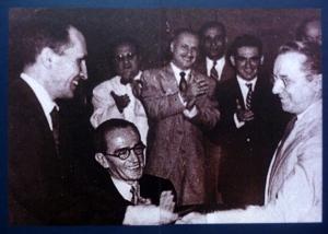 Portinari reçoit sa carte de membre du PCB des mains de Luis Carlos Prestes, secrétaire général du parti, devant l'écrivain Graciliano Ramos (assis à gauche) / DR